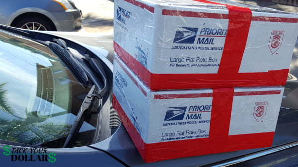 Two military care packages in large flat rate usps boxes on car